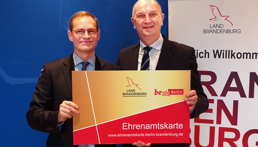 Michael Müller und Dietmar Woidke mit der neuen Ehrenamtskarte (Foto: brandenburg.de)